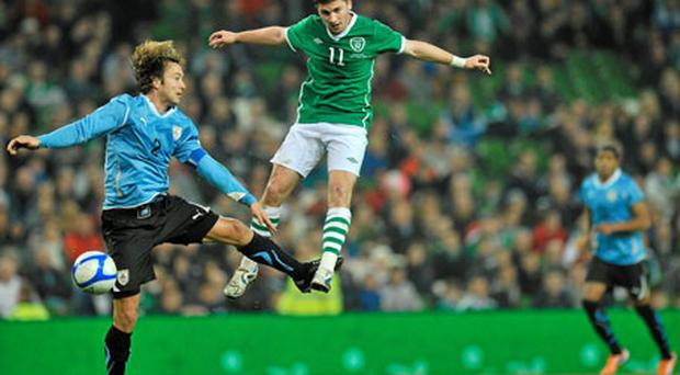Ireland's Shane Long jumps for the ball alongside Uruguay's Diego Lugano at Lansdowne Road last night. Photo: David Maher / Sportsfile