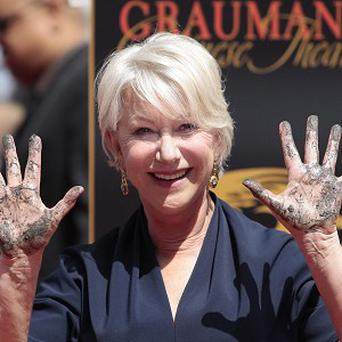 Helen Mirren shows her cement-covered hands during a ceremony at Grauman's Chinese Theatre in Los Angeles