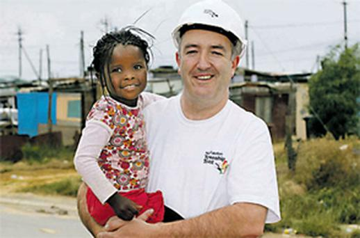 Developer Niall Mellon meets a young resident of Wallacedene township, South Africa