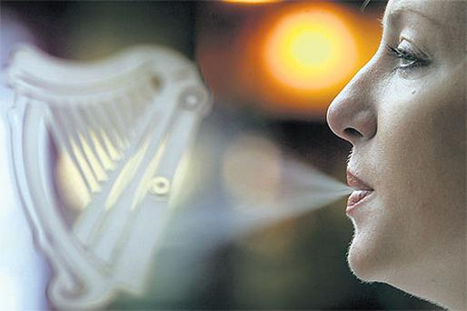 A woman smokes outside a Dublin bar, after the introduction of the ban in 2004