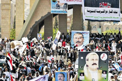 Supporters of Yemeni President Ali Abdullah Saleh hold his posters and wave their national flag during a rally supporting him in Sanaa,Yemen, yesterday. Photo: HANI MOHAMMED