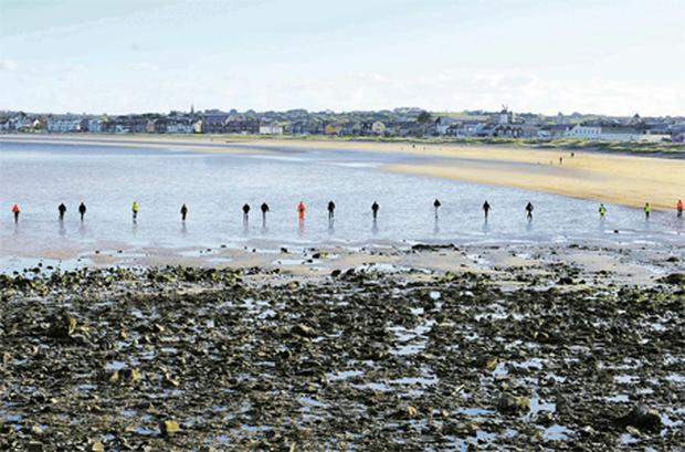 A team of volunteers carries out a search on south Skerries Beach in Dublin yesterday