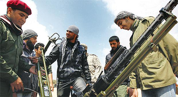 Rebel volunteers get training on how to use an anti-aircraft gun at a military camp in Benghazi