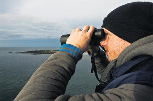 Patrick Hughes, who raised the alarm over his missing friends, looks out to sea through binoculars