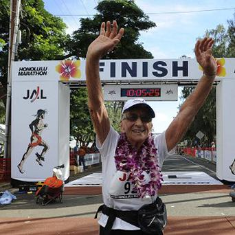 Gladys Burrill crosses the finish line at the end of the Honolulu Marathon (AP)