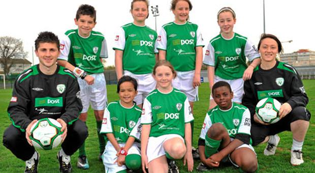 Ireland internationals Shane Long and Megan Campbell with, back row, left to right, Luke O'Shaughnessy, Sofie Hamilton, Megan Hamilton, Isobel O'Farrell, front row left to right, Pethina Santos, Abbey McCarthy and Sean Oluwasanni at the launch of the FAI An Post Summer Soccer Schools Programme yesterday. Photo: David Maher / Sportsfile