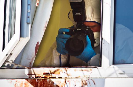 Forensic gardai attempt to find clues amid the bloodstains on the windows at the Dublin home of Violet Quigley, who suffered multiple wounds in the attack and lost a significant amount of blood. Photo: MARK CONDREN