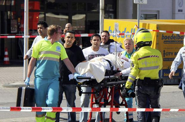 CARNAGE: Police officers and an ambulance surround the shopping centre after the mass shooting near Amsterdam yesterday. Injured people are carried out of the mall. Photo: AP