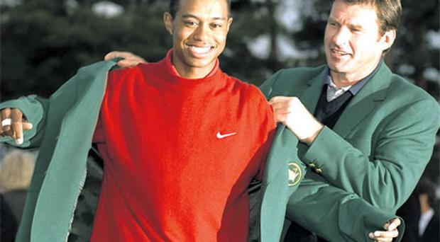 1996 Masters champion Nick Faldo helps Tiger Woods on with the green jacket following Woods' victory in 1997.