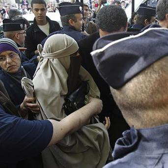 An unidentified veiled woman is taken away by police officers in Paris (AP)