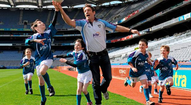 Kildare manager Kieran McGeeney jumps for a ball with Charlie McCarthy (8) and his sister Kate (6) from Dublin, at the launch of the VHI GAA Cúl Camps in Croke Park yesterday.