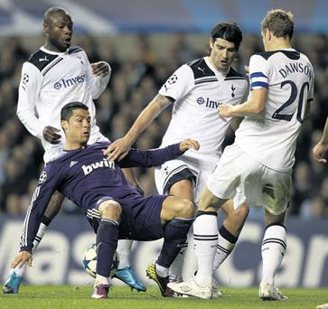 Madrid's goalscorer Cristiano Ronaldo is upended under pressure from Tottenham's Vedran Corluka and Michael Dawson (R).