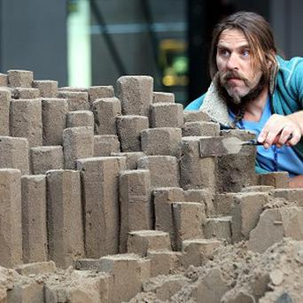 Yorkshire-born sand sculptor Paul Hoggard creates the Giant's Causeway from sand in the Victoria centre shopping complex in Belfast