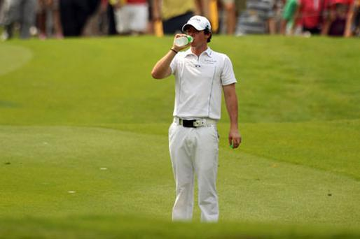 Rory McIlroy takes a drink during the first round of the Malaysian Open in Kuala Lumpur yesterday. Photo: Getty Images