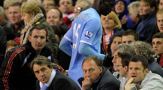 Manchester City manager Roberto Mancini looks away from Mario Balotelli after substituting him during Monday's defeat at Anfield. Photo: Getty Images