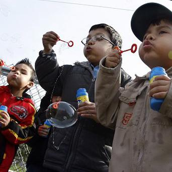 Children join an effort to break the world record for the most people blowing bubbles at the same time (AP)