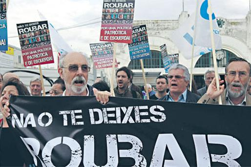 Protesters outside Portugal's finance ministry in Lisbon yesterday with a banner that reads