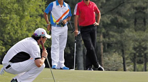 YOUNG GUNS: Rickie Fowler (C) and Jason Day (R) watch Rory McIlroy line up a putt on the 18th green during second round play in this year's Masters.