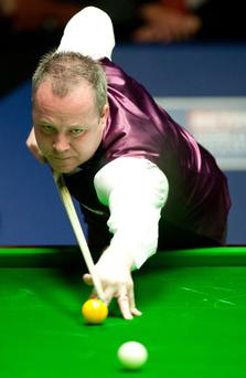 John Higgins plays a shot in his first round game against Stephen Lee. Photo: PA