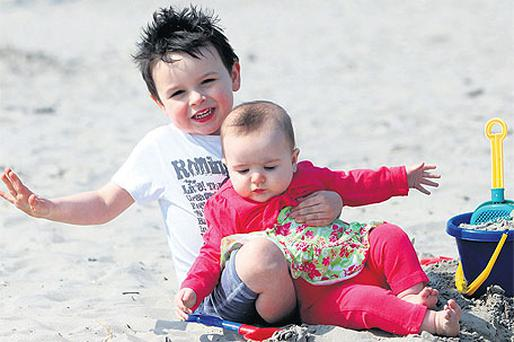 Daniel McInerney (3) and his sister Isabelle (6 months), from Tallaght, had fun on Dollymount Strand on the other side of Dublin Bay