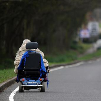 A disabled grandmother in a mobility scooter headbutted a mugger when three youths ambushed her