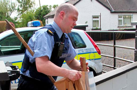 A garda removes a sledgehammer and crowbar from the home of the postmistress near Prosperous, Co Kildare. Photo: Collins