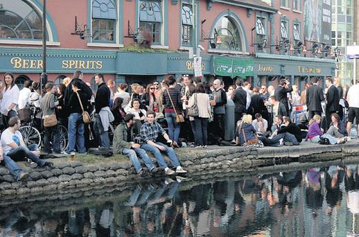 ON THE WATERFRONT: Workers enjoy the good weather as they begin the Easter bank holiday break outside the Barge pub on Charlemont Street in Dublin. Photo: Gerry Mooney