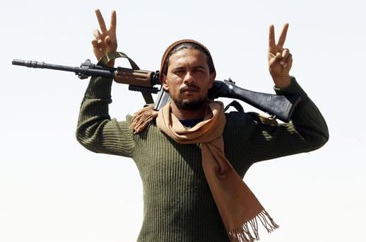 A rebel fighter does victory gestures. Photo: Reuters