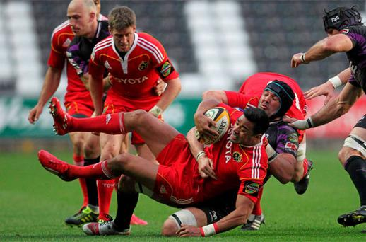 Lifeimi Mafi, Munster, is tackled by Jonathan Thomas, Ospreys.