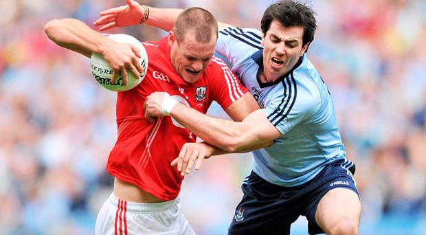 Dublin's Michael Darragh Macauley tussles with Cork's Pearse O'Neill during yesterday's Allianz Football League Division 1 final at Croke Park. Photo: DAVID MAHER / SPORTSFILE