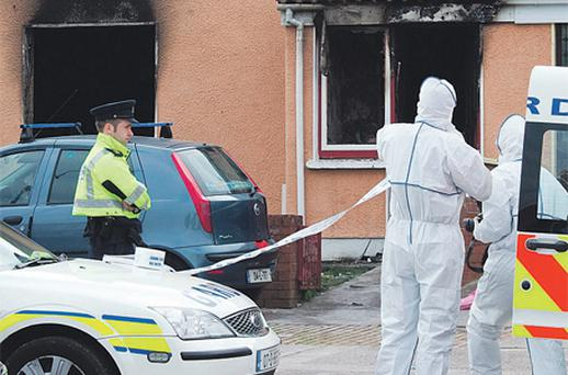 Garda forensic officers outside the house that was gutted in a suspected arson attack in Mahon, Cork city