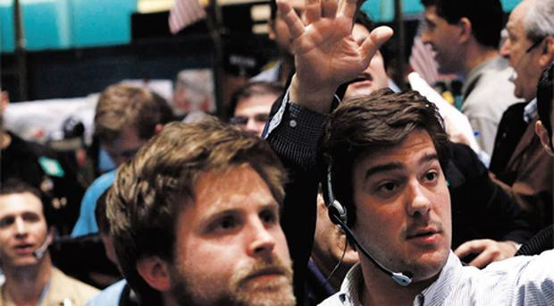 Traders work in the silver and gold options pit on the floor of the New York Mercantile Exchange in New York on Monday. Spot silver surged more than 5pc to above $49 an ounce, buoyed by a weak dollar and strong physical demand in Asia that also propelled gold to a record high for a seventh consecutive session. Photo: Reuters