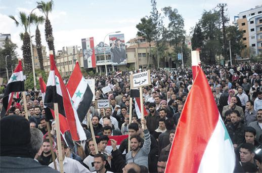 Protesters are seen holding placards during a demonstration in Douma town, Syria, earlier this month. The Syrian government is appealing to the minorities – the Christians and the Kurds – to stay loyal