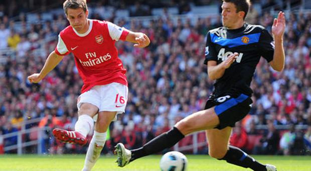Arsenal's Aaron Ramsey shoots past Michael Carrick for what turned out to be the winning goal. Photo: Getty Images