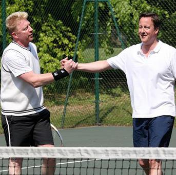 Prime Minister David Cameron shakes hands with Boris Becker during a charity tennis match at Chequers