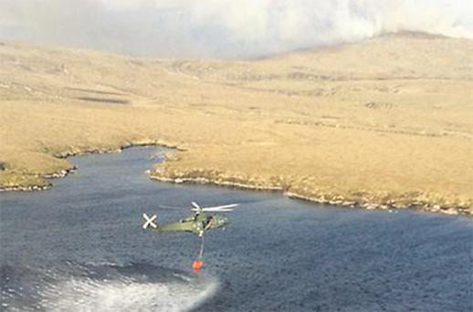 An aerial photo from the Defence Forces shows a helicopter scooping up water to pour on the gorse fire in Donegal