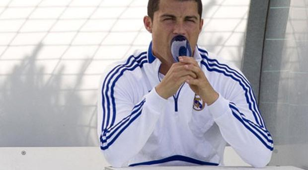 Cristiano Ronaldo is all alone with his thoughts as he sits on a bench before training with Real Madrid yesterday ahead of tonight's clash with Barcelona. Photo: AP