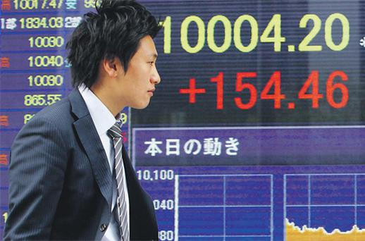 An electronic stock board shows the closing price of the Nikkei outside a securities firm in Tokyo, Japan, yesterday