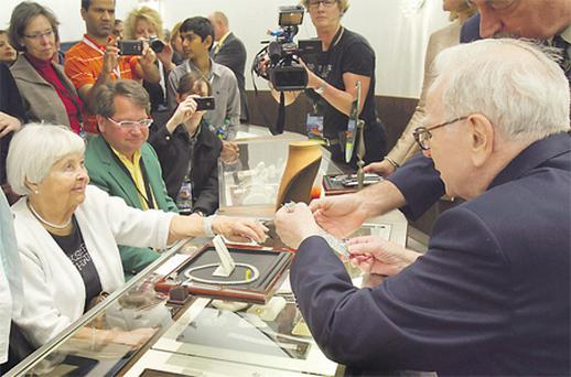 Billionaire investor Warren Buffett, chairman and CEO of Berkshire Hathaway, sells jewellery to shareholder Patsy Hosman of Jefferson, South Dakota, at the Berkshire-owned Borsheims jewellery store in Omaha, Nebraska, during a well-attended AGM at the weekend, where 40,000 turned up to fete the 'Sage of Omaha'