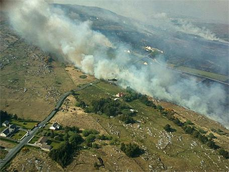A Defence Forces helicopter pours water on a large gorse fire in Co Donegal
