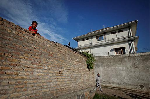 A boy looks over a wall in front of the compound where Osama bin Laden was killed in Abbottabad