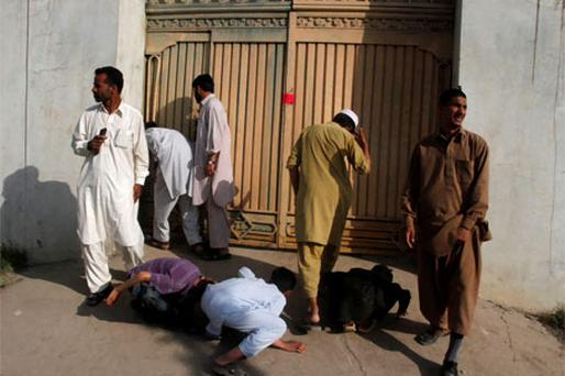 Local residents try to look past the gates into the compound where Osama bin Laden was killed