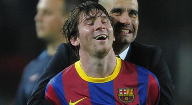 Barcelona coach Pep Guardiola congratulates Lionel Messi after the Catalans booked their Champions League final place. Photo: AP