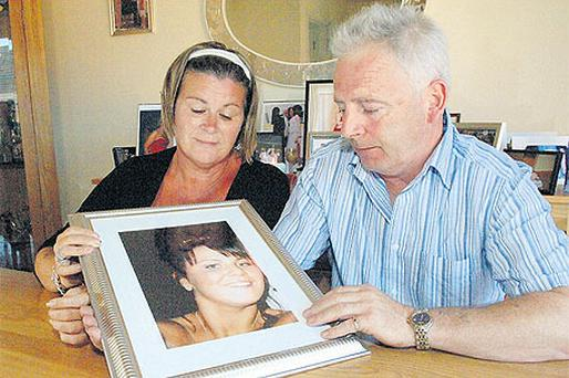 Colette and Anthony Wolfe, with a picture of their teenage daughter Leanne, who took her own life after suffering six years of bullying at school