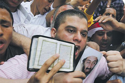 Islamist protesters gathered in Cairo yesterday, holding pictures of Osama bin Laden and copies of the Koran