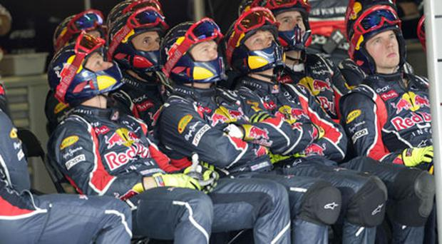 Red Bull crew members watch their driver Sebastien Vettel on the TV screens in the pit-box as he powers to victory in yesterday's Turkish Grand Prix. Photo: Reuters