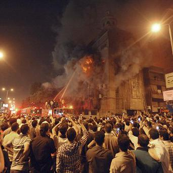 Firemen fight a fire at a church surrounded by angry Muslims in Cairo (AP)