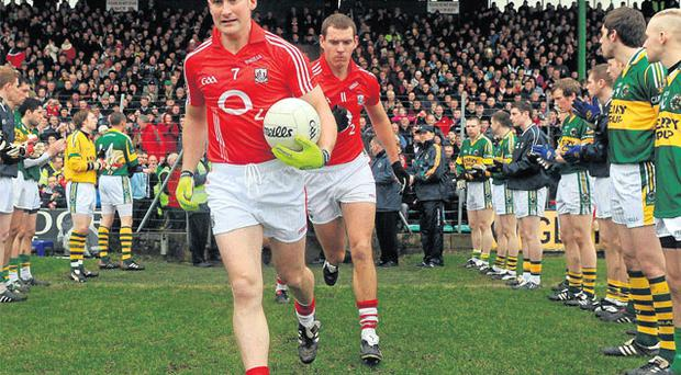 Cork defender Noel O'Leary leads the team out as Kerry players form a guard of honour for the All-Ireland champions ahead of the league clash in Tralee last February
