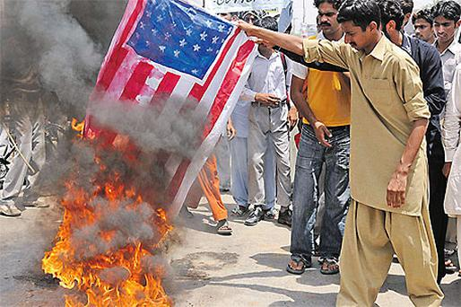Supporters of Pakistan's Muslim League burn a representation of the US flag during an anti-American demonstration in Multan, Pakistan, yesterday