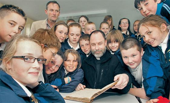 Rev Michael Johnston points out to pupils from Shinrone NS the entry of the marriage of Barack Obama's ancestor Joseph Kearney to Sarah Healy in the church registry book